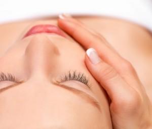Closeup of young woman receiving face massage