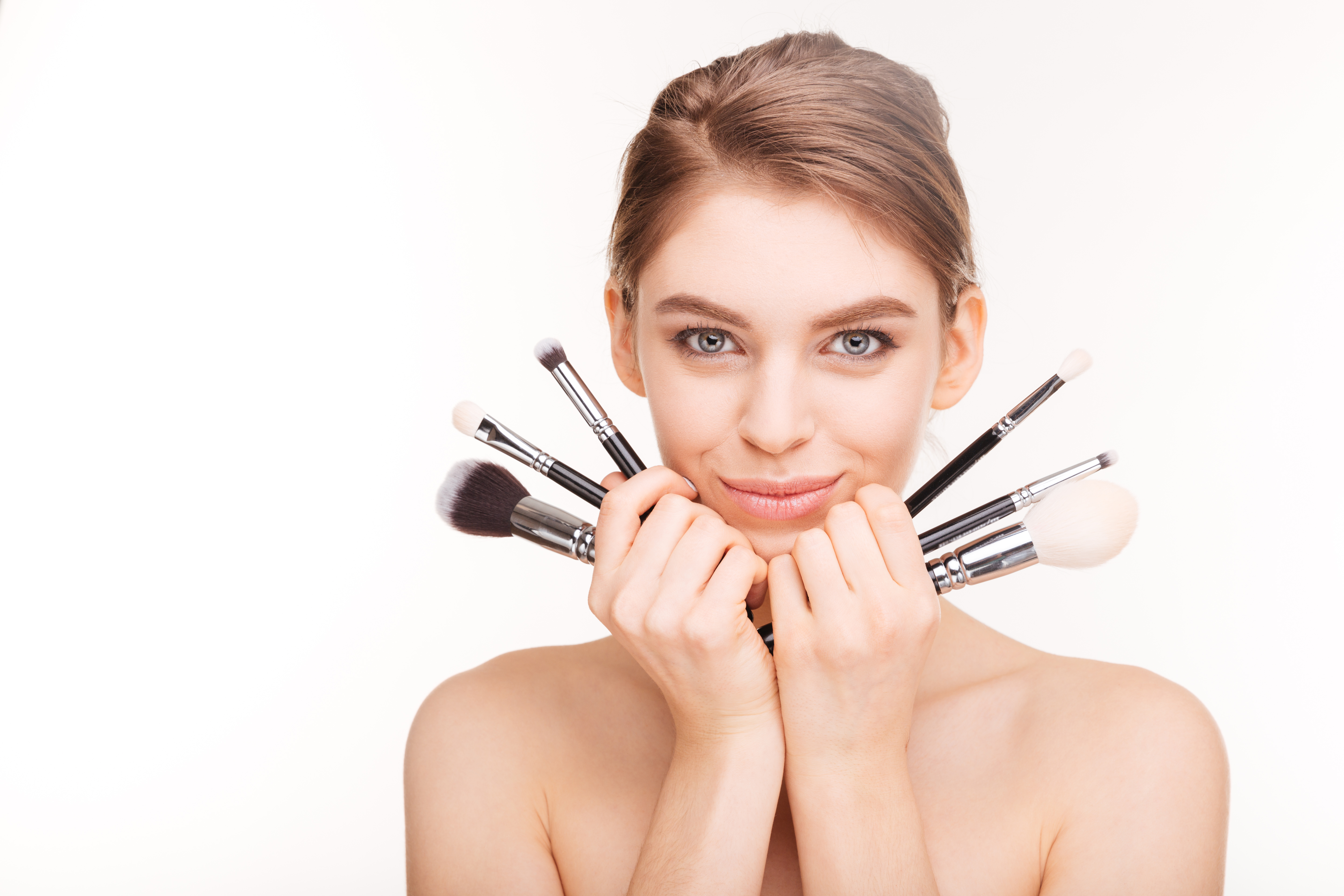 pretty smiling young woman with makeup brushes
